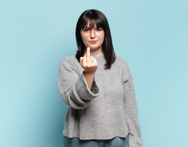 Plus size pretty woman feeling angry, annoyed, rebellious and aggressive, flipping the middle finger, fighting back