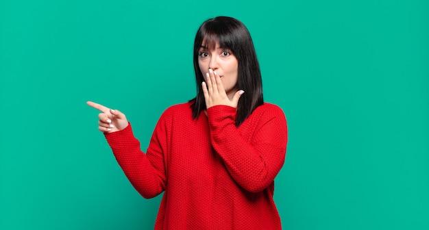 Симпатичная женщина больших размеров чувствует себя счастливой, шокированной и удивленной, прикрывая рот рукой и указывая на боковую копию