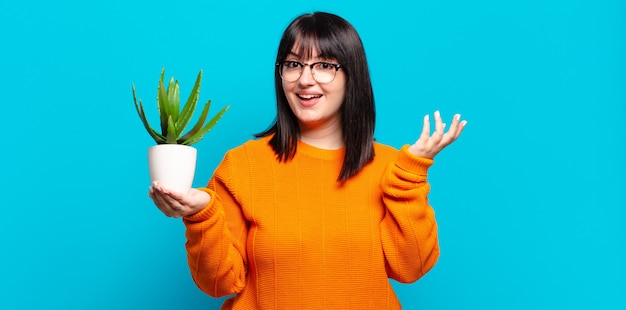 Plus size pretty woman feeling happy, surprised and cheerful, smiling with positive attitude, realizing a solution or idea