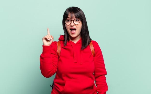 Симпатичная женщина больших размеров, реализовавшая идею, почувствовала себя счастливой и взволнованной гением, весело подняв палец, эврика!