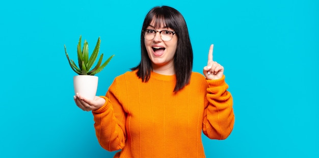 Plus size pretty woman feeling like a happy and excited genius after realizing an idea, cheerfully raising finger, eureka!