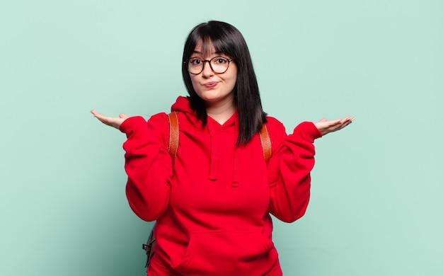 プラスサイズのきれいな女性は、戸惑い、混乱し、疑ったり、重みを付けたり、面白い表現でさまざまなオプションを選択したりします