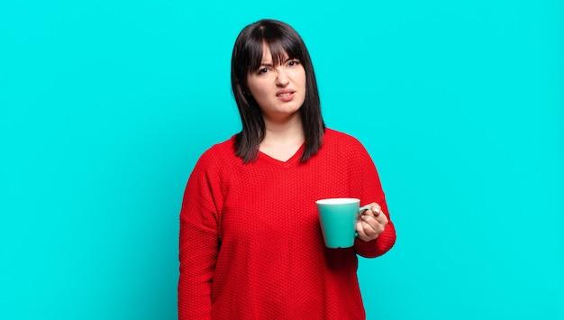 プラスサイズのきれいな女性は、予想外の何かを見ている愚かな、唖然とした表情で、困惑して混乱していると感じています