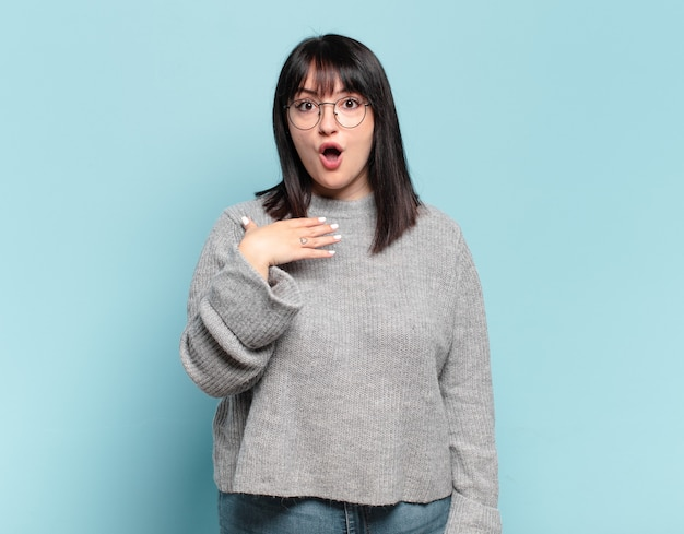 Plus size pretty woman feeling shocked, astonished and surprised, with hand on chest and open mouth, saying who, me?