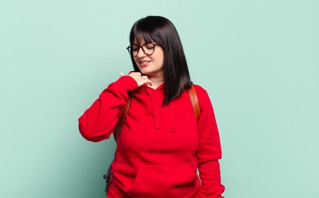 Симпатичная женщина больших размеров чувствует стресс, тревогу, усталость и разочарование, потянув за шею рубашки