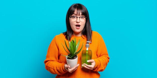 Плюс размер красивая женщина, держащая кактус. концепция алоэ вера
