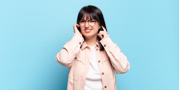 怒って、ストレスを感じてイライラしているように見えるプラスサイズのきれいな女性は、耳をつんざくような音で両耳を覆っています
