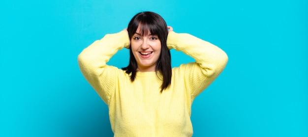 Симпатичная женщина больших размеров выглядит счастливой, беззаботной, дружелюбной и расслабленной, наслаждаясь жизнью и успехом, с позитивным настроем