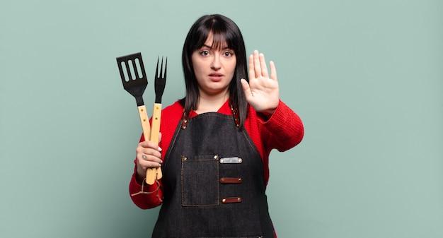 Симпатичная женщина больших размеров выглядит серьезной, строгой, недовольной и сердитой, показывая открытую ладонь, делая жест стоп