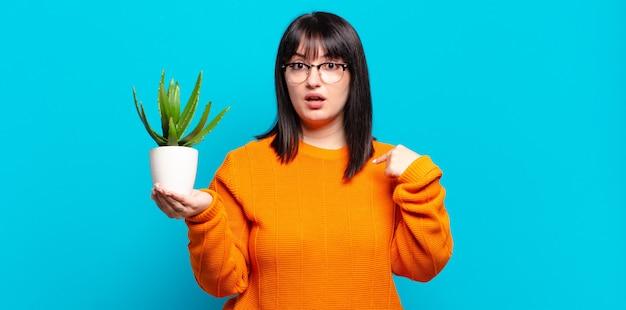 プラスサイズのきれいな女性は、口を大きく開いてショックを受けて驚いたように見え、自分を指しています