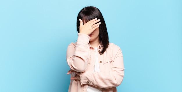 プラスサイズのきれいな女性は、ストレス、恥ずかしがり屋、または動揺して、頭痛で、手で顔を覆っています