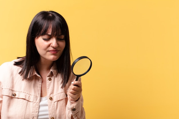 Plus size pretty woman looking with a magnifying glass