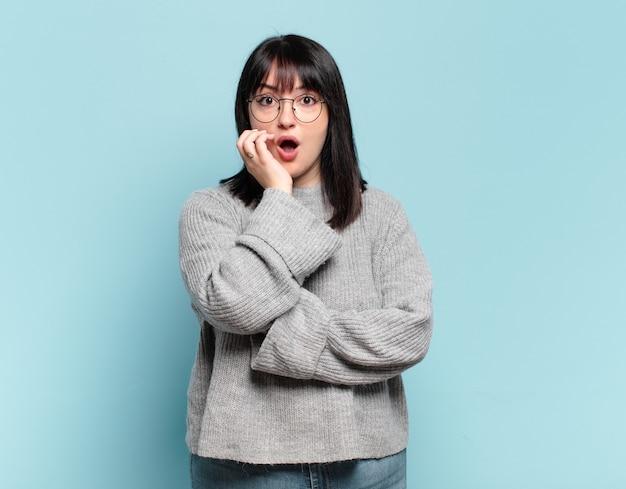 プラスサイズのきれいな女性は、ショックと不信感で口を開け、頬と腕を組んで、愚かで驚いています。