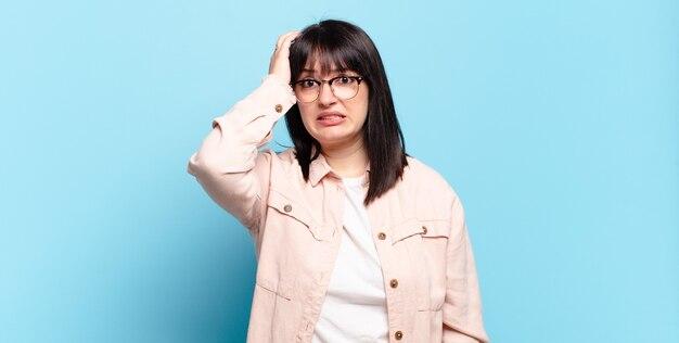 Симпатичная женщина больших размеров паникует из-за забытого дедлайна, чувствует стресс, вынуждена скрывать беспорядок или ошибку