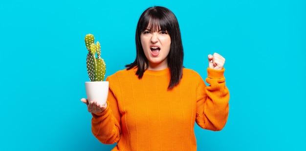 Симпатичная женщина больших размеров агрессивно кричит с гневным выражением лица или со сжатыми кулаками, празднуя успех