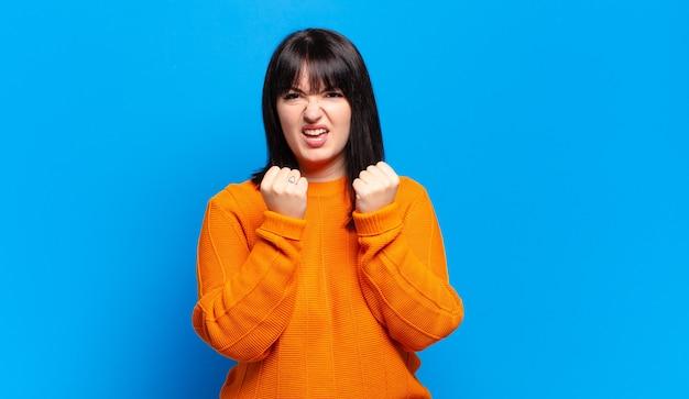 プラスサイズのきれいな女性は、イライラした、欲求不満の、怒った表情とタイトな拳で積極的に叫び、激怒を感じます