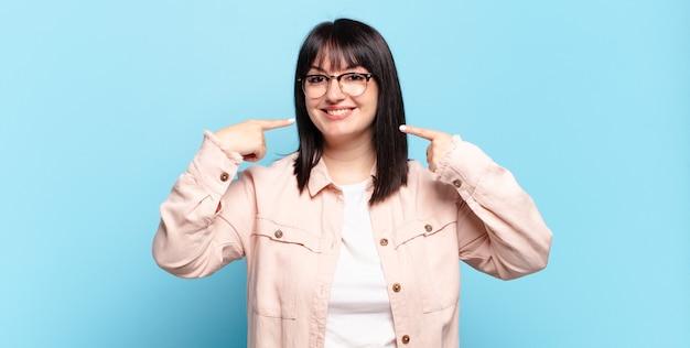 プラスサイズのきれいな女性が自信を持って笑顔で自分の広い笑顔、前向きでリラックスした、満足した態度を指しています