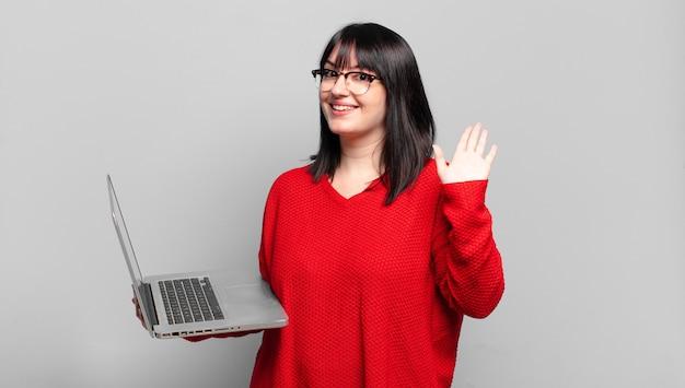 プラスサイズのきれいな女性は、楽しく元気に笑ったり、手を振ったり、歓迎して挨拶したり、さようならを言ったりします