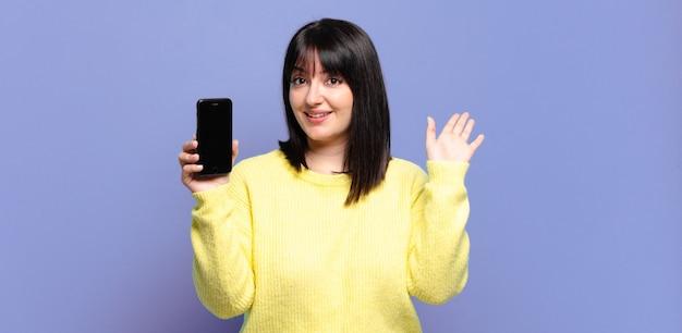 Симпатичная женщина больших размеров счастливо и весело улыбается, машет рукой, приветствует и приветствует вас или прощается