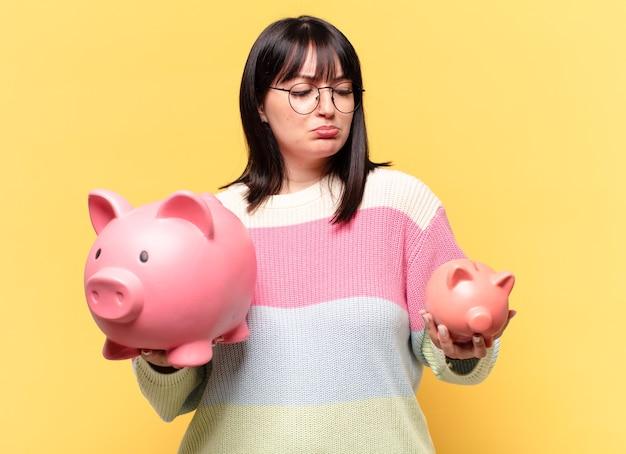 貯金箱を持つプラスサイズのきれいな女性。貯蓄の概念