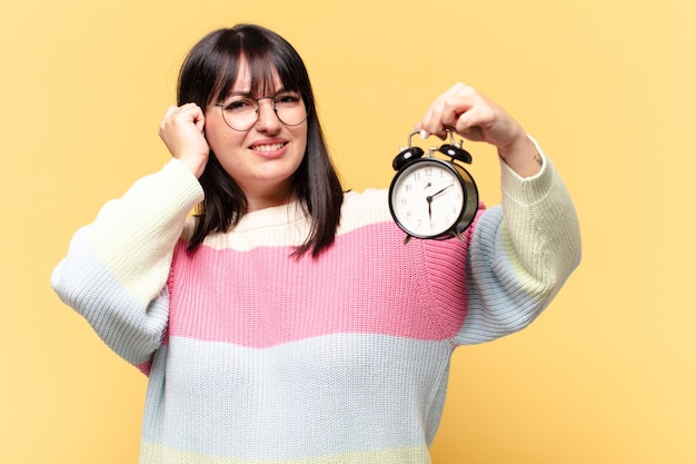 Plus size pretty woman with an alarm clock