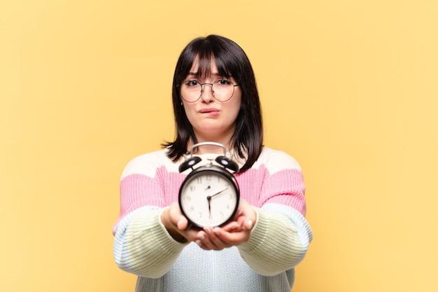 目覚まし時計付きプラスサイズのきれいな女性