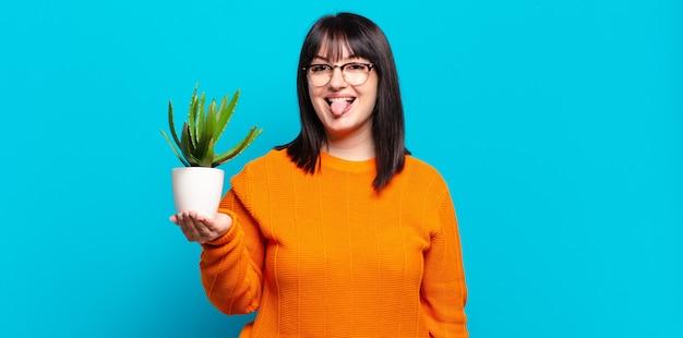 Симпатичная женщина больших размеров с веселым, беззаботным, бунтарским настроем, шутит и высунула язык, веселится