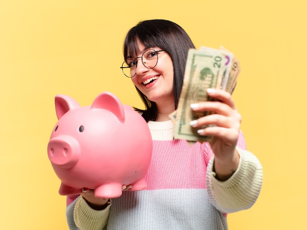 Plus size pretty woman with a piggy bank. savings concept