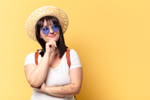Plus size pretty woman with sunglasses and a hat on holidays