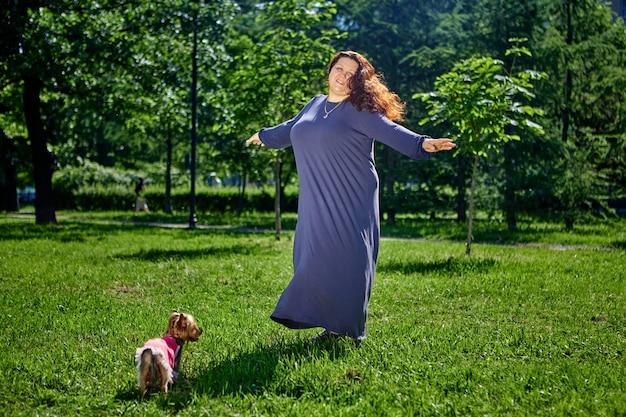 長い夏のドレスで芝生の上で踊るプラスサイズの女性