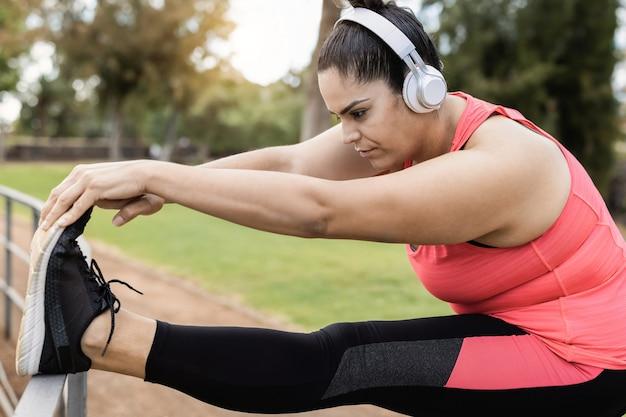 Женщина больших размеров делает упражнения на растяжку на открытом воздухе в городском парке