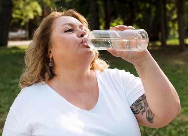 プラスサイズの女性が公園で水を飲む