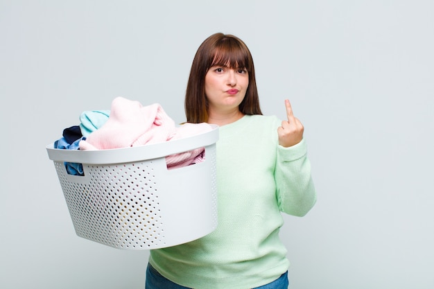 Plus size woman feeling angry, annoyed, rebellious and aggressive, flipping the middle finger, fighting back