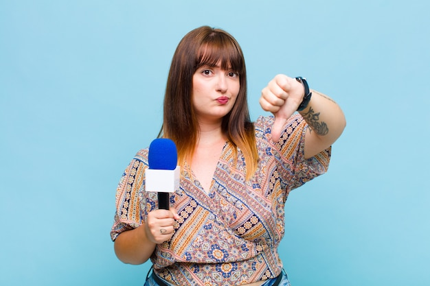 Plus size woman feeling cross, angry, annoyed, disappointed or displeased, showing thumbs down with a serious look