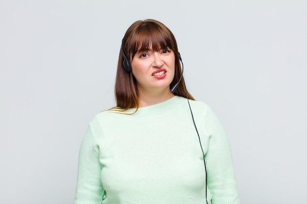 더하기 크기의 여성은 예상치 못한 것을보고 멍청하고 기절 한 표정으로 당혹스럽고 혼란스러워합니다.