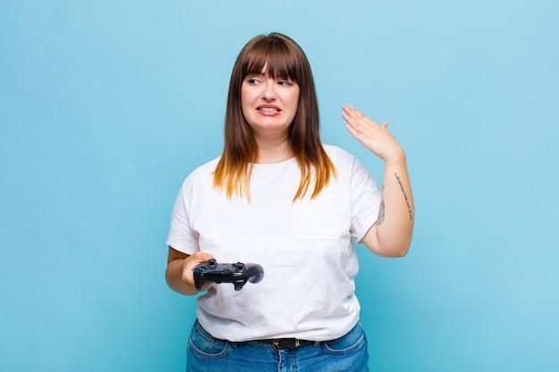 Женщина больших размеров чувствует стресс, тревогу, усталость и разочарование, тянет рубашку за шею, выглядит расстроенной проблемой