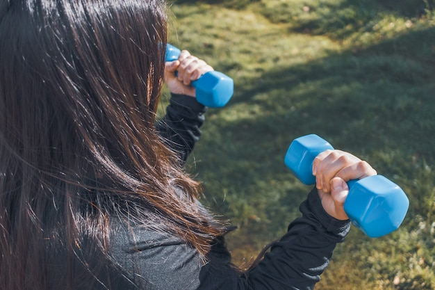 Plus size woman holding two blue dumbbells healthy life fitness concept