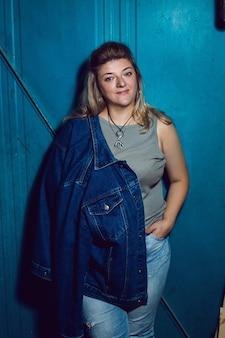 데님 재킷과 파란색 바지를 입은 플러스 사이즈 여성이 울타리 옆에 서 있습니다.