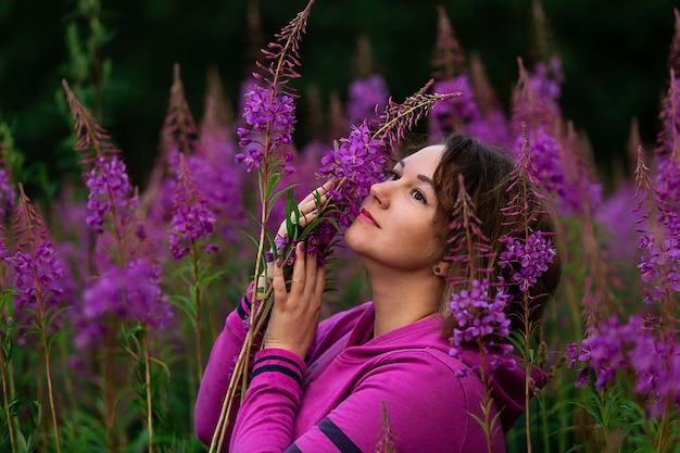 田舎の牧草地の明るい花の中に立っている間脇を見てフクシアパーカーのプラスサイズの女性