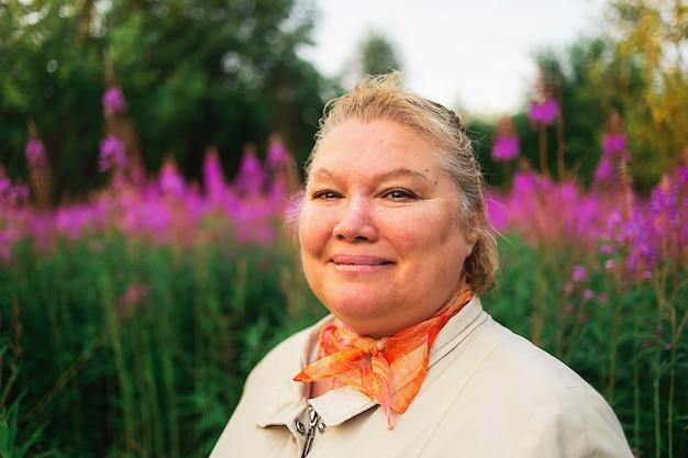 田舎の牧草地の明るい花の中で立っている間カメラを見ているフクシアパーカーのプラスサイズの女性