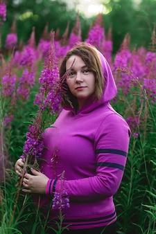 牧草地の明るい花の中に立っている間カメラを見ているフクシアパーカーのプラスサイズの女性