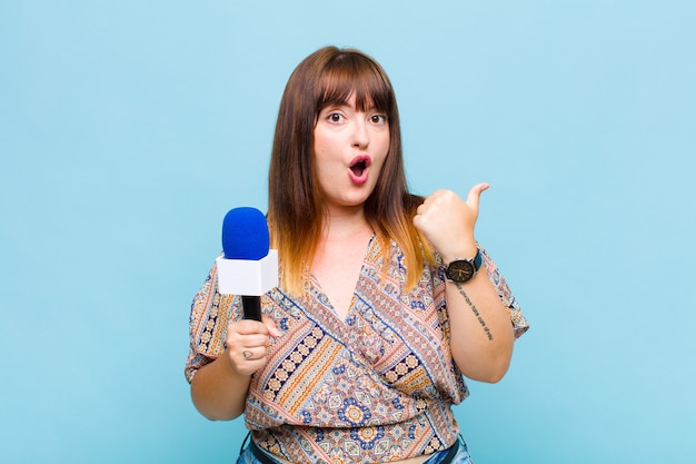 Plus size woman looking astonished in disbelief, pointing at object on the side and saying wow, unbelievable