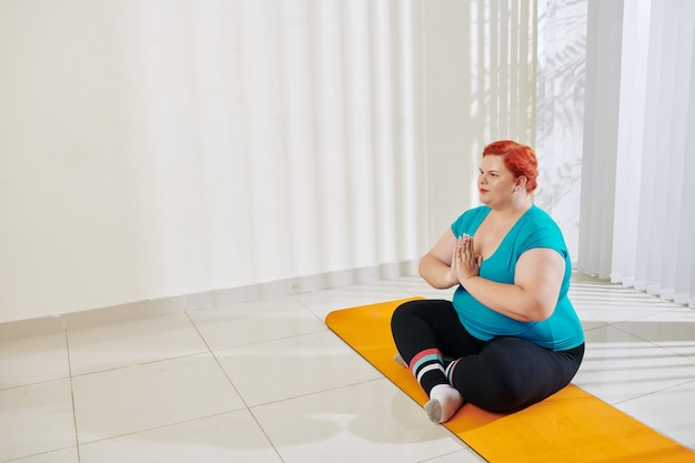 Plus size woman in lotus position