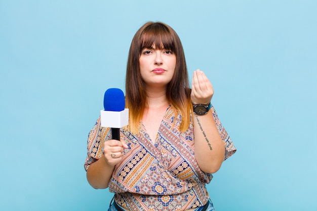 Plus size woman making capice or money gesture, telling you to pay your debts!