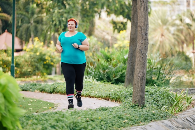 Plus size woman running in park