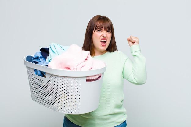 Женщина большого размера агрессивно кричит с гневным выражением лица или со сжатыми кулаками, празднуя успех