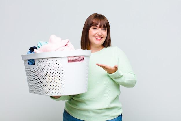 プラスサイズの女性は元気に笑顔、幸せを感じ、手のひらでコピースペースでコンセプトを示しています