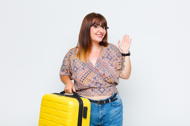 Plus size woman smiling happily and cheerfully, waving hand, welcoming and greeting you, or saying goodbye