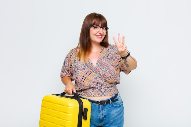 Plus size woman smiling and looking friendly, showing number one or first with hand forward, counting down