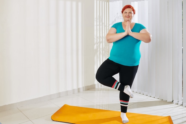 Plus size woman standing in tree pose